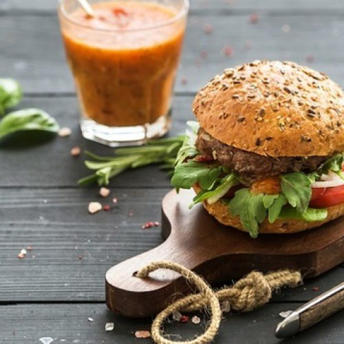 fresh-homemade-burger-on-dark-serving-board-with-spicy-tomato